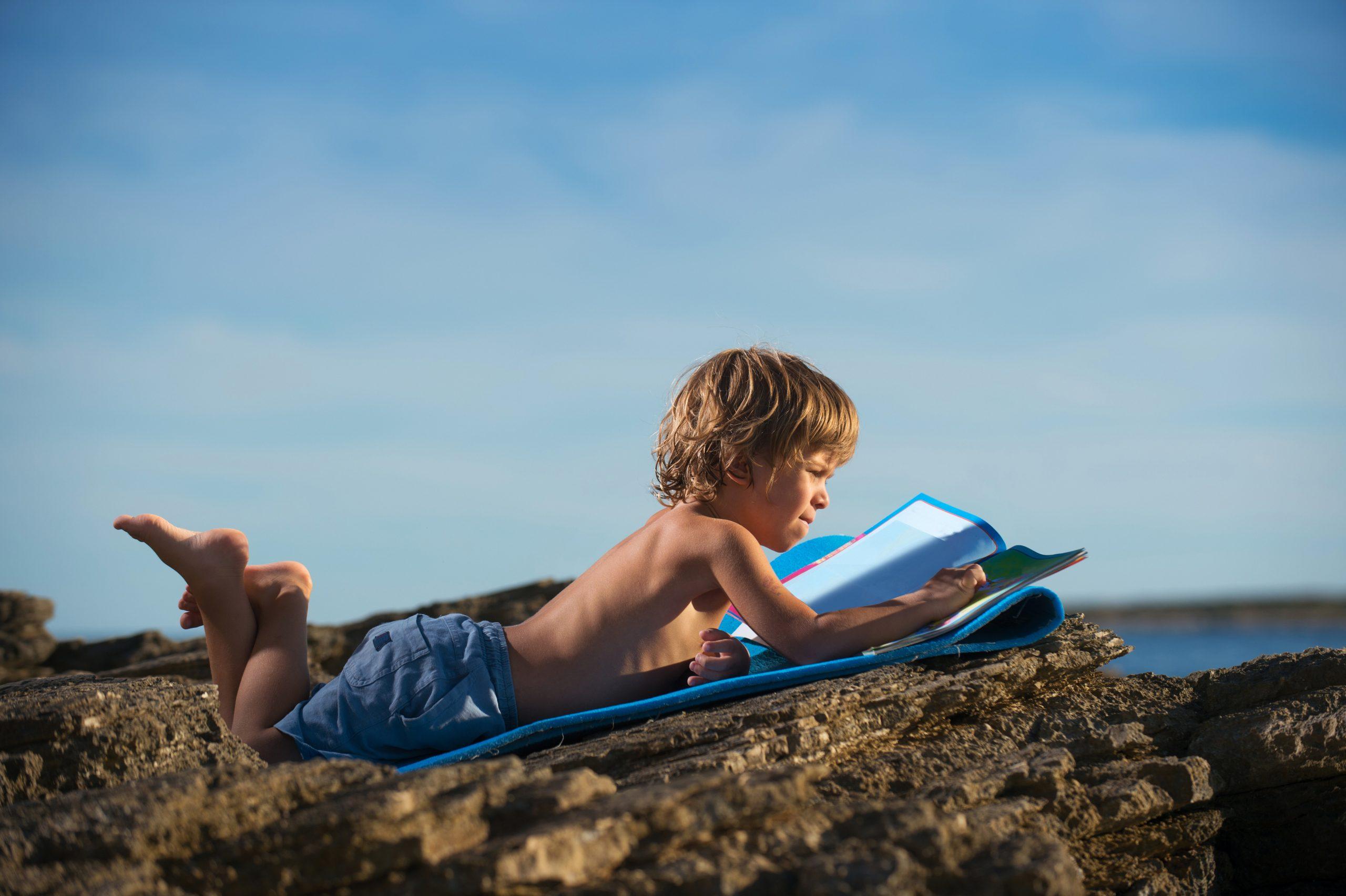 enfant sur la plage avec son cahier de vacances