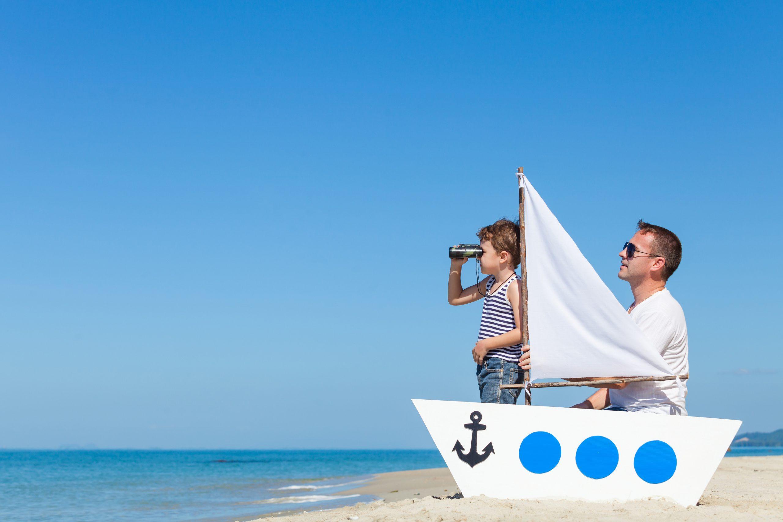 Père et fils jouent sur une barque à la plage